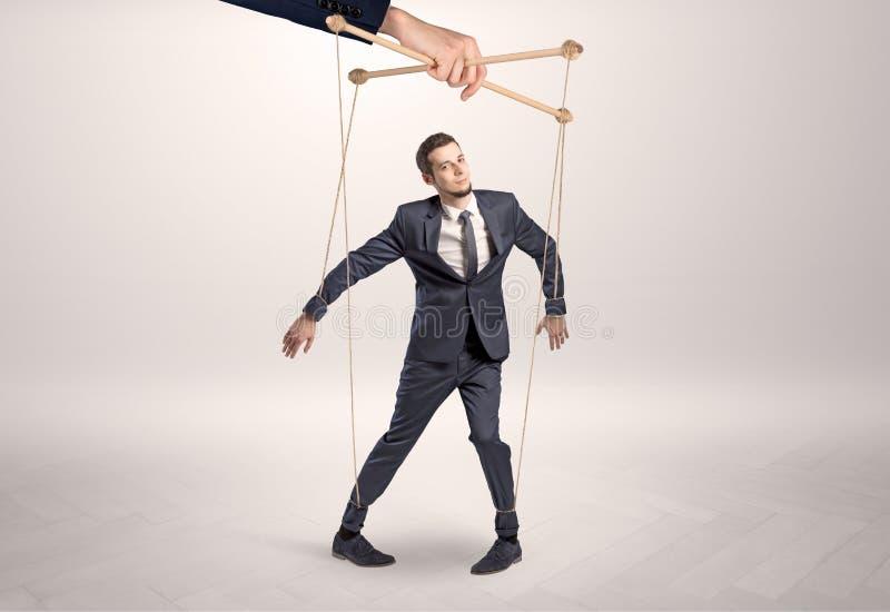 Marionettengeschäftsmann verbleit durch eine riesige Hand lizenzfreie stockfotos