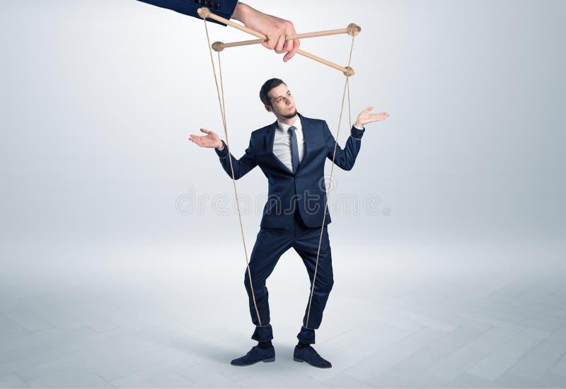 Marionettengeschäftsmann verbleit durch eine riesige Hand stockfotografie
