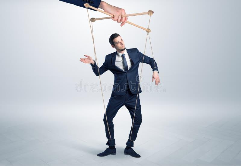 Marionettengeschäftsmann verbleit durch eine riesige Hand stockbild