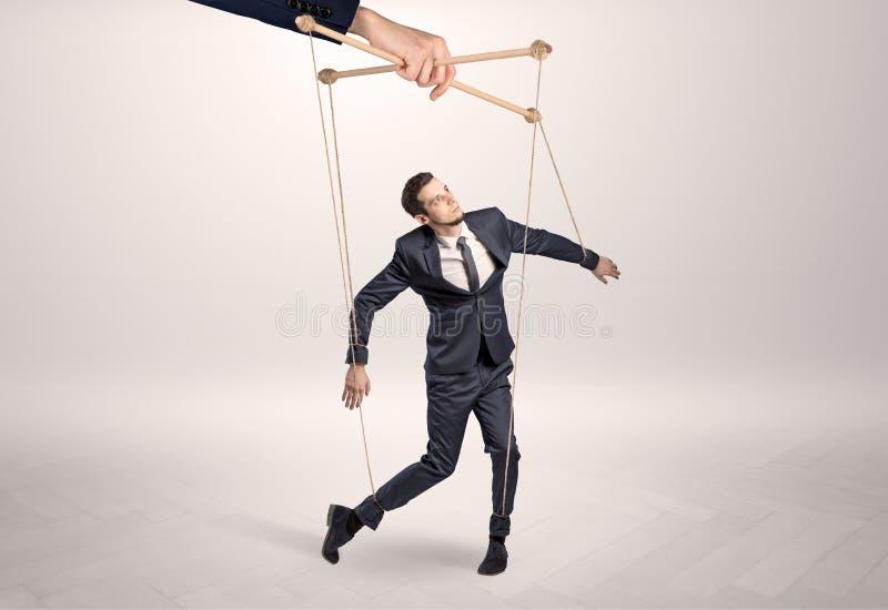 Marionettengeschäftsmann verbleit durch eine riesige Hand stockfotos