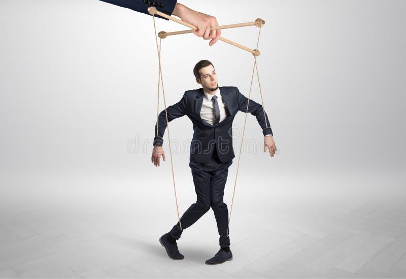 Marionettengeschäftsmann verbleit durch eine riesige Hand lizenzfreies stockbild