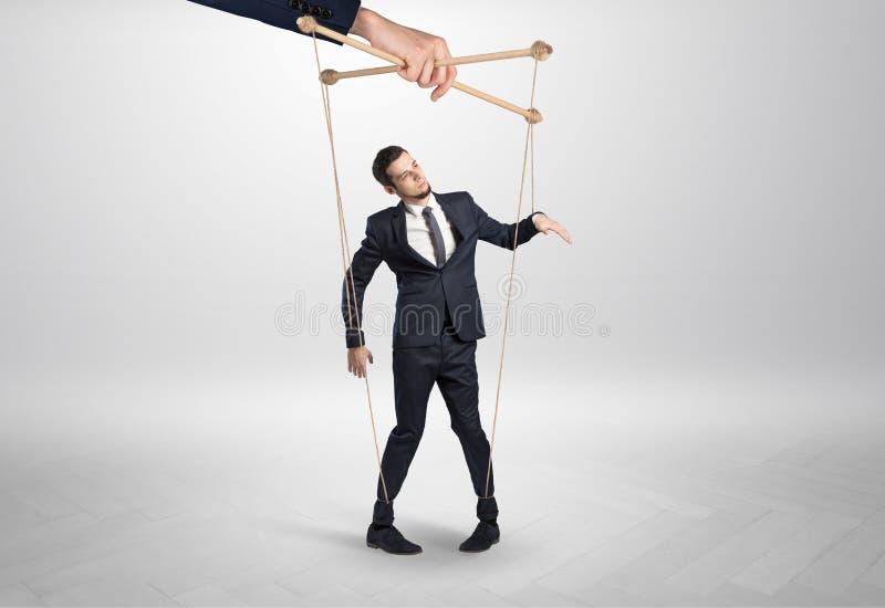 Marionettengesch?ftsmann verbleit durch eine riesige Hand lizenzfreie stockbilder