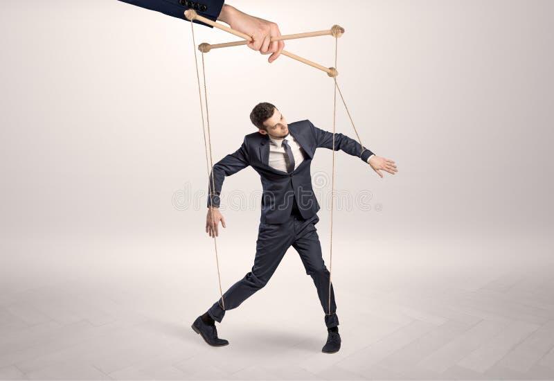 Marionettengesch?ftsmann verbleit durch eine riesige Hand lizenzfreies stockfoto