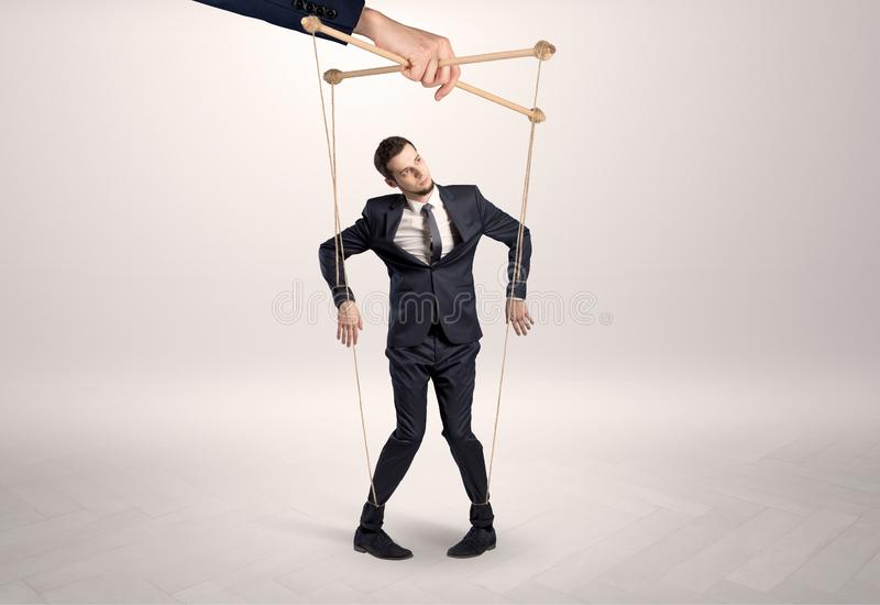 Marionettengesch?ftsmann verbleit durch eine riesige Hand lizenzfreies stockbild