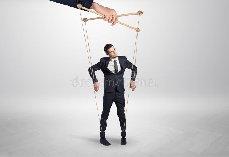 Marionettengesch?ftsmann verbleit durch eine riesige Hand stockfoto