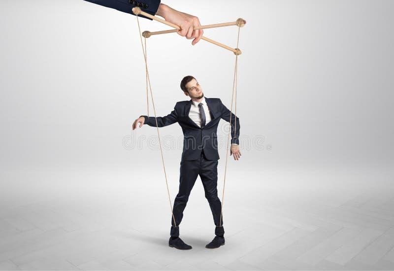 Marionettengesch?ftsmann verbleit durch eine riesige Hand stockfotografie