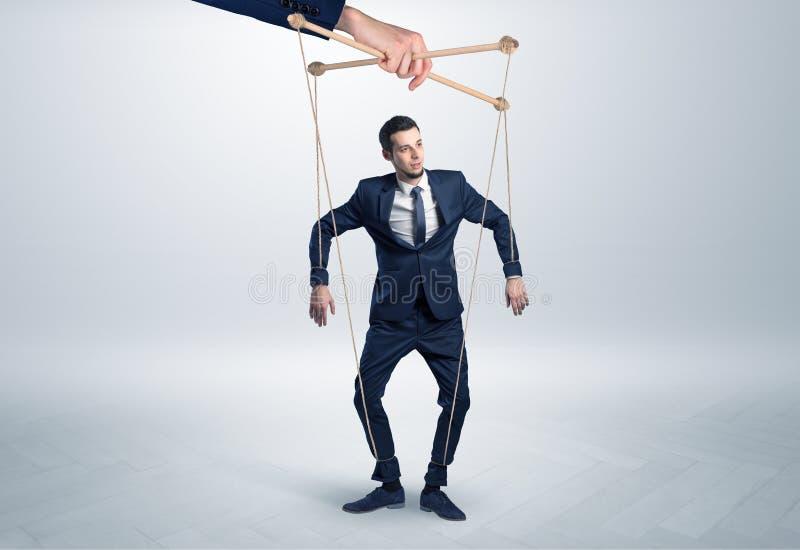 Marionettenzakenman leaded door een reusachtige hand stock fotografie