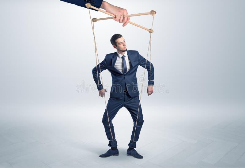 Marionettenzakenman leaded door een reusachtige hand stock foto