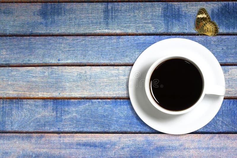 Mariposa de la taza de café en de madera imagenes de archivo