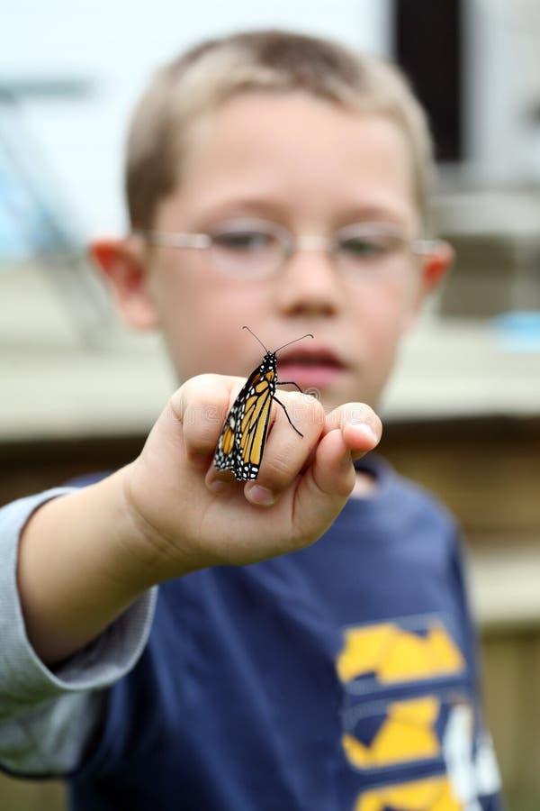 Mariposa de monarca joven de la explotación agrícola del muchacho foto de archivo