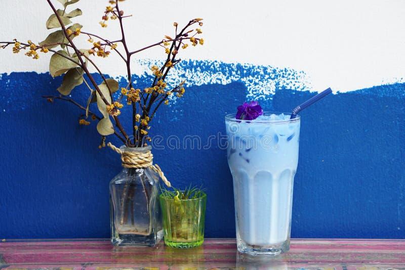 Mariposa helada Pea Latte con el palillo de la leche y de canela en la tabla de madera imagen de archivo