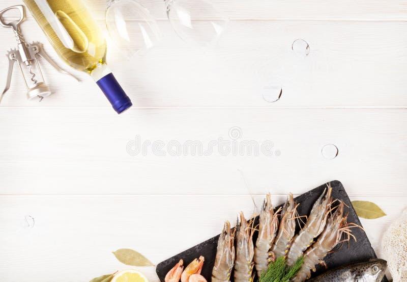 Marisco crudo fresco con las especias y la botella del vino blanco imagenes de archivo