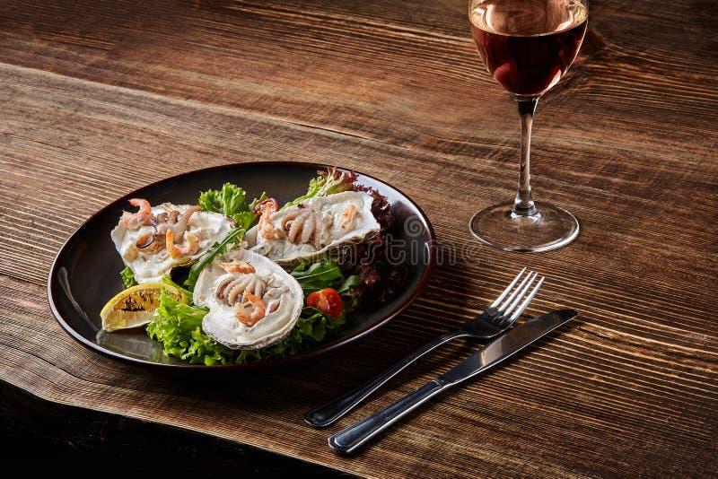 Marisco Culinária do restaurante, alimento de guloseimas saudável Ostras, camarões, polvo no molho de creme branco no shell de fotografia de stock royalty free