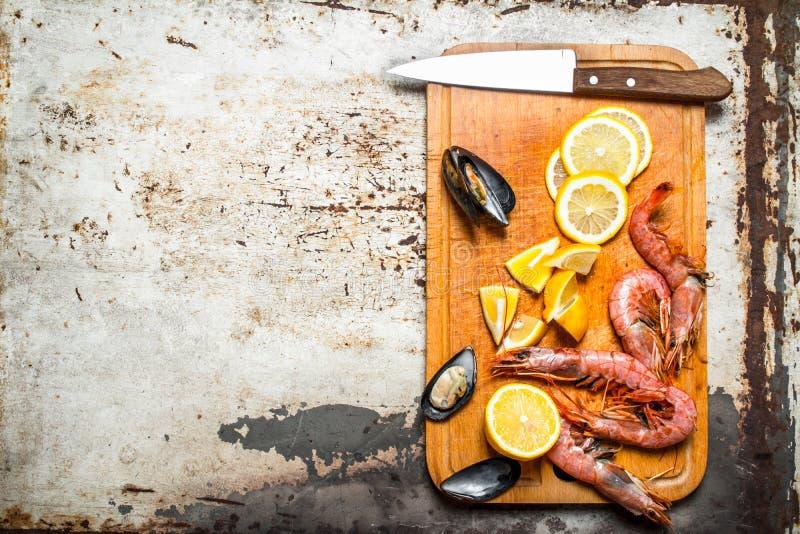 Marisco fresco Placa de corte com camarão, marisco e limão foto de stock royalty free