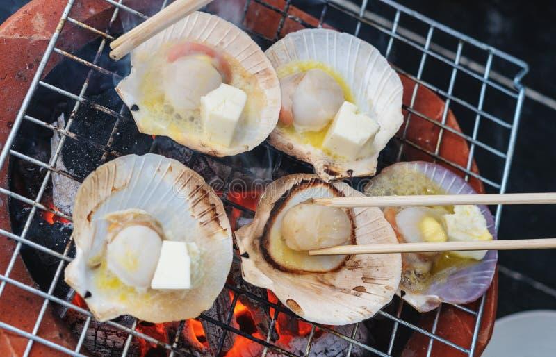 Mariscos asados a la parrilla, concha de peregrino con mantequilla y ajo en estufa del carbón de leña imagen de archivo