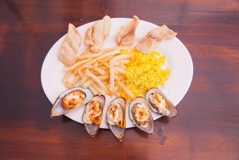 Mariscos con las patatas fritas y el arroz imágenes de archivo libres de regalías