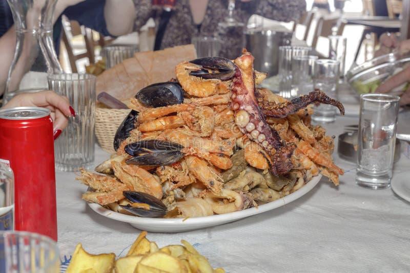 Mariscos diversos, fritos en un primer grande del plato imagenes de archivo
