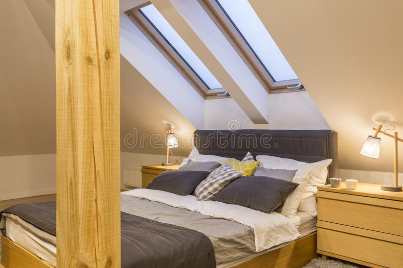 Marital bed at the attic. With bedside cabinet stock photography