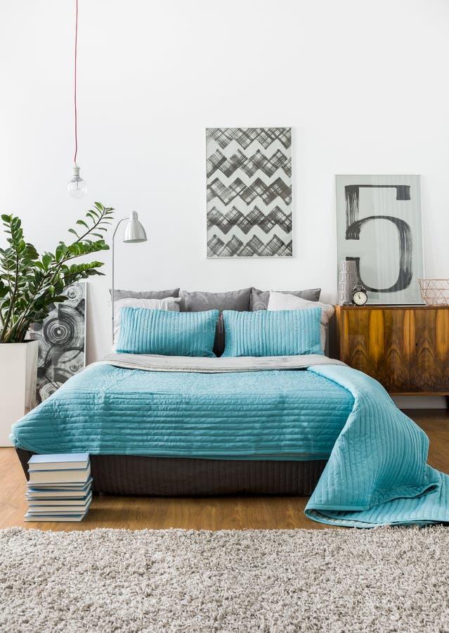 Marital bed in cozy bedroom. Turquoise bedspread on marital bed in cozy bedroom stock photography