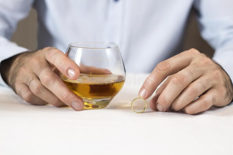 Marital problems. Hands of a man sitting at a white table are holding a glass of whiskey. The other hand is holding a wedding. Marital problems. The hands of a royalty free stock images