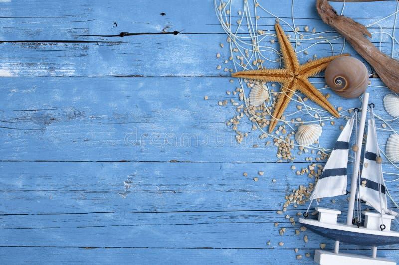 Maritieme Decoratie met shells, zeester, varend schip, visnet op blauw afwijkingshout stock foto's