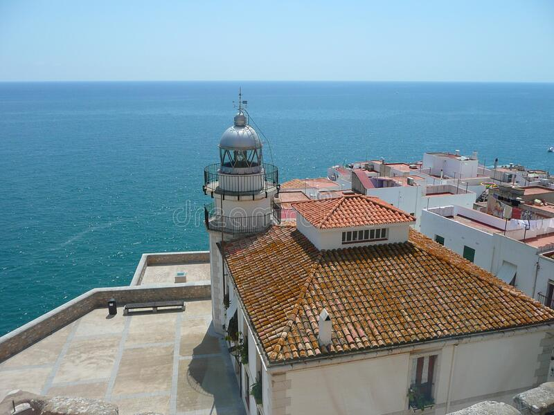 Lighthouse with the sea in the background and white houses with tiled roofs in the foreground, Peñíscola, Castellón, Spain. Maritime lighthouse with the stock photos