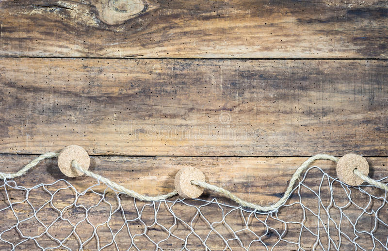 Maritime nautical decoration with fishnet, seashells and fish decoration. Fishing net with sea shells and fish decoration on old brown wooden boards and place royalty free stock images