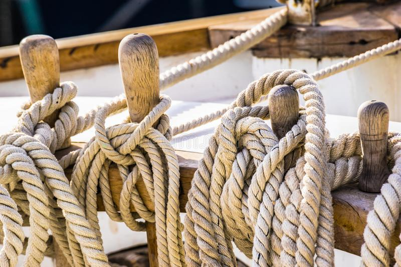 Maritime nautical ropes, knotted on wooden cleats of old sailing boat. Old sailboat, detail closeup of wooden cleats with tied nautical ropes stock images