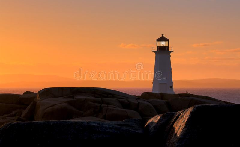 A Maritime Sunset. An iconic figure on the maritime coast. The lighthouse at Peggy's Cove in Nova Scotia, Canada royalty free stock image