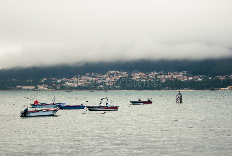 Mysterious maritime town, boats and fog. A maritime village is seen behind a river with boats royalty free stock image