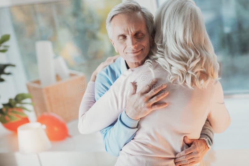 Marito anziano allegro che abbraccia la sua moglie immagini stock libere da diritti