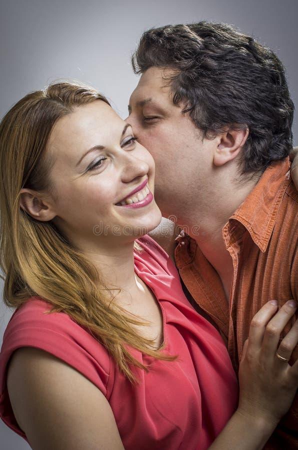 Marito che dice un segreto alla sua moglie fotografia stock