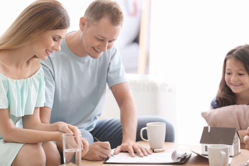 Marito che firma un contratto per la casa d'acquisto in ufficio dell'agente immobiliare fotografia stock libera da diritti