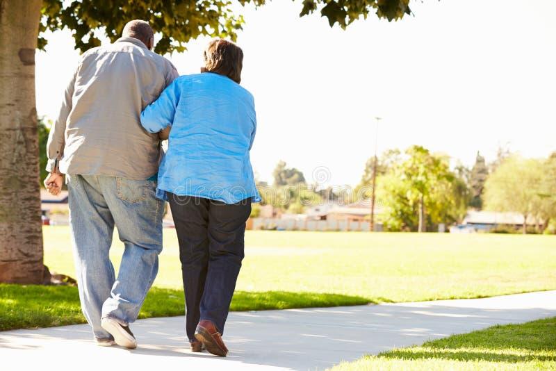 Marito d'aiuto della donna senior come camminano insieme in parco immagini stock