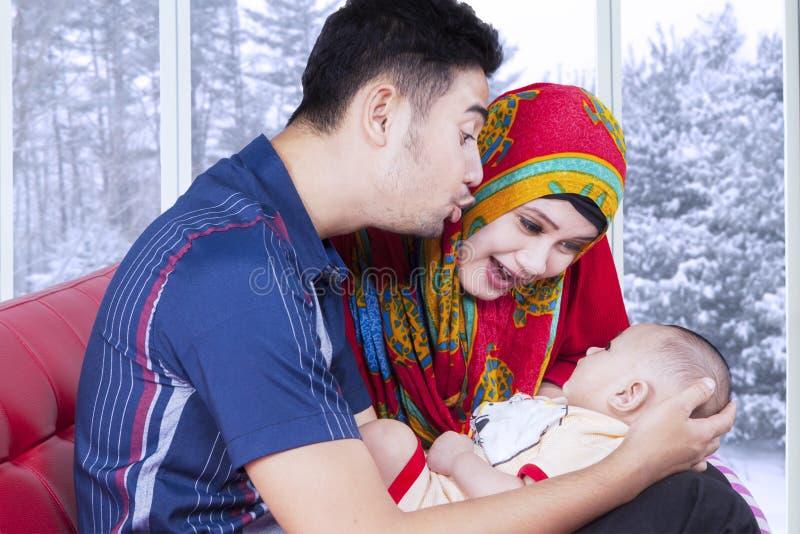 Marito e moglie che giocano con il bambino sullo strato fotografie stock libere da diritti