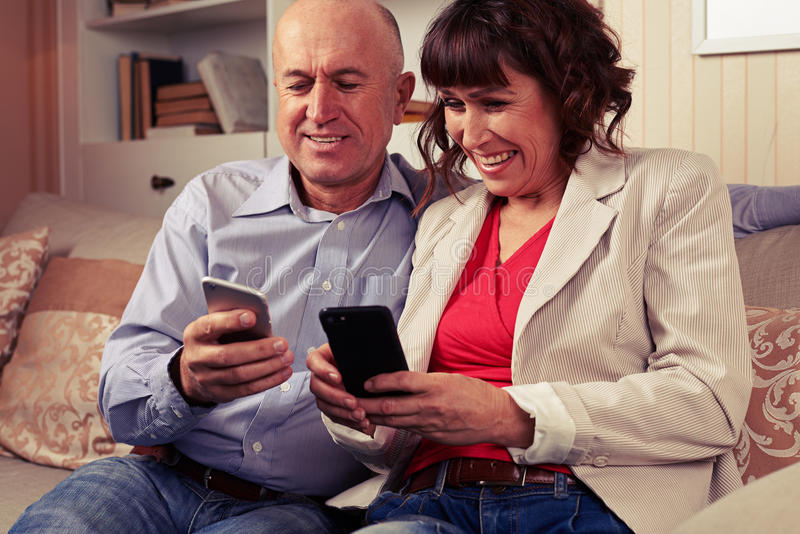 Marito e moglie che sorridono e che esaminano i telefoni immagini stock