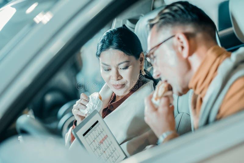 Marito e moglie pranzando nell'automobile immagine stock libera da diritti