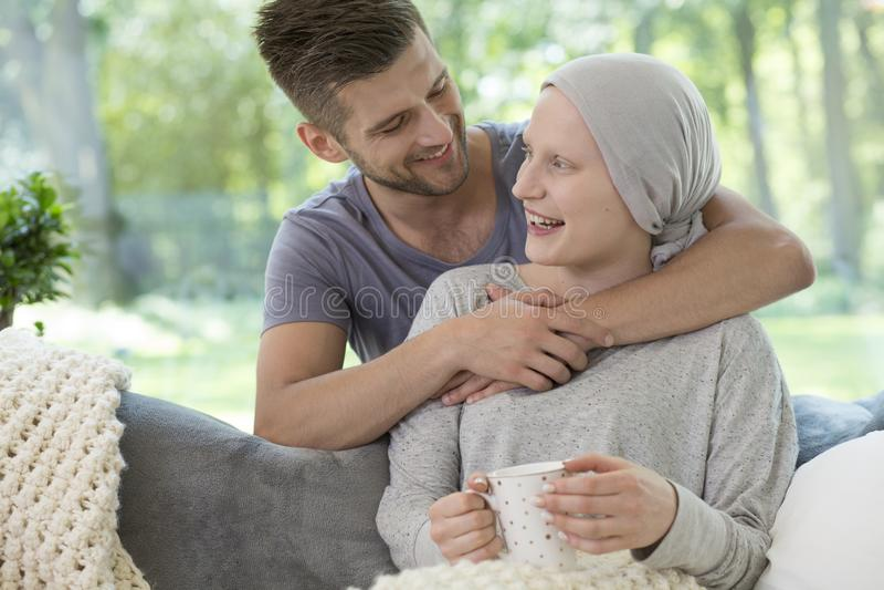 Marito felice che abbraccia la sua moglie che recupera dalla chemioterapia per fotografia stock libera da diritti