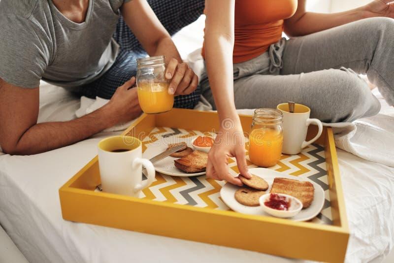 Marito felice e moglie che mangiano prima colazione a letto immagini stock libere da diritti