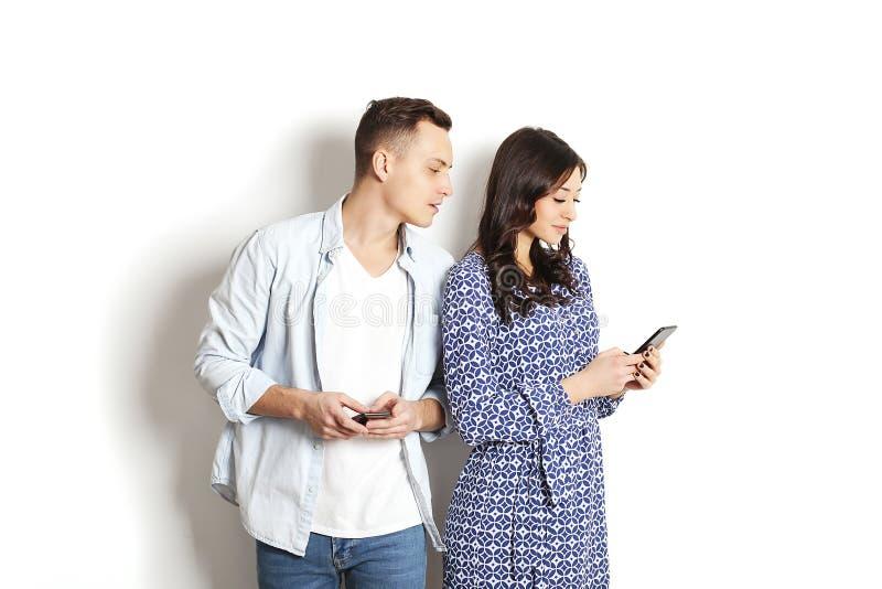 Marito geloso che spia il suo telefono cellulare della moglie mentre sta leggendo un messaggio Concetto di relazione & di tecnolo immagini stock