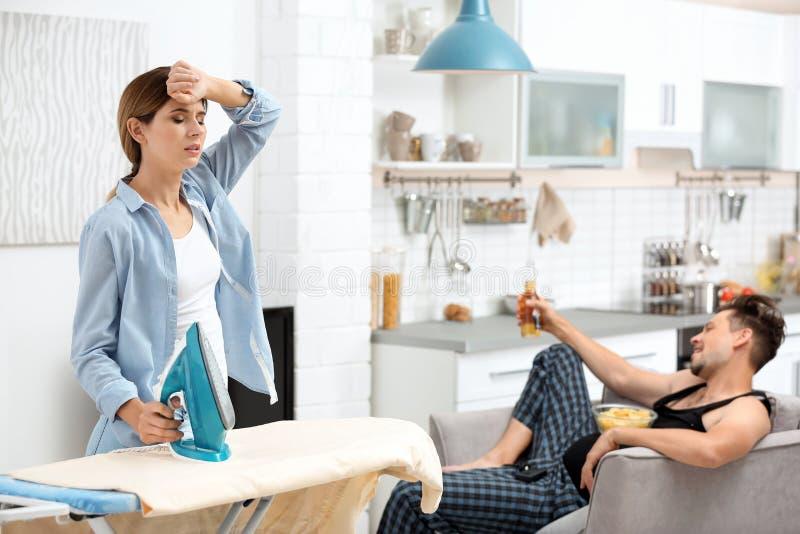 Marito pigro che guarda TV e suo rivestire di ferro della moglie immagini stock