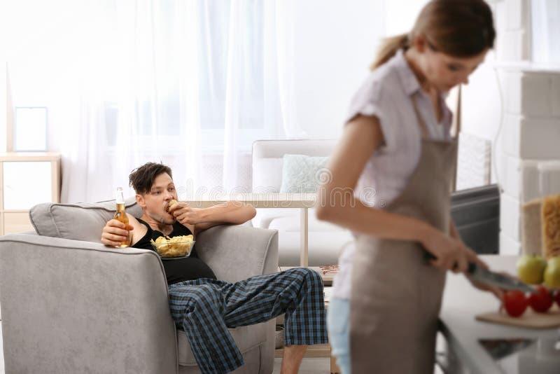 Marito pigro che guardano TV e la sua moglie immagine stock libera da diritti