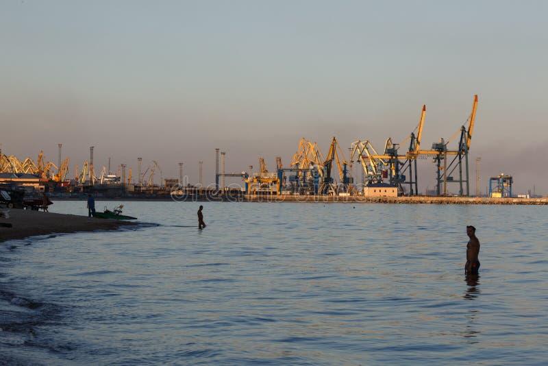 MARIUPOL, DE OEKRAÏNE - SEPTEMBER 5, 2016: Vele groot kranensilhouet in de haven bij gouden licht van zonsondergang stock foto's