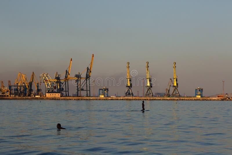 MARIUPOL, UKRAINE - 5 SEPTEMBRE 2016 : Silhouette de beaucoup grande de grues dans le port à la lumière d'or du coucher du soleil photo stock