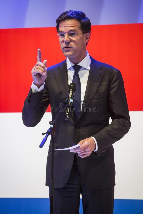 Mark Rutte que lleva a cabo un discurso delante de la bandera holandesa imagen de archivo