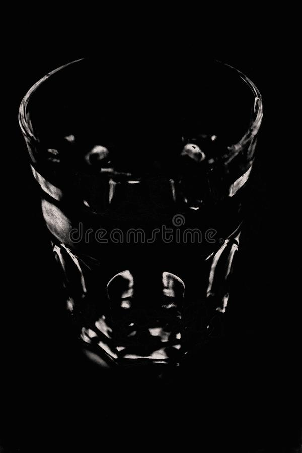 Marked black and white image, the black of the background is struck by small white spots that show a glass. royalty free stock images