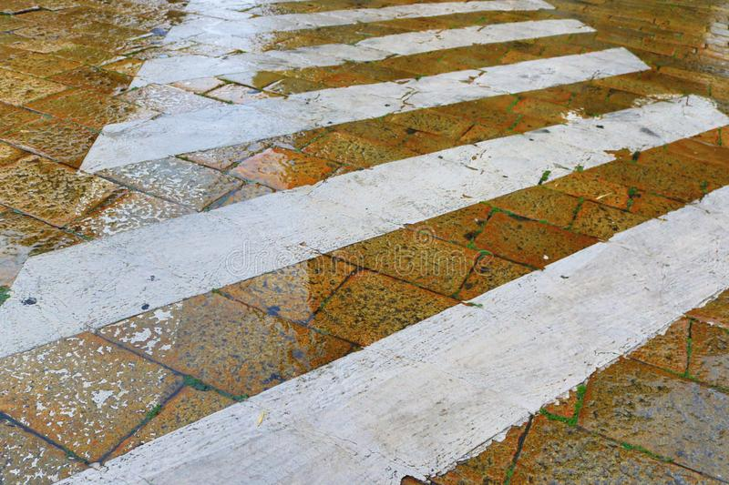 Marked pedestrian crossing wet old cobbled street royalty free stock photography