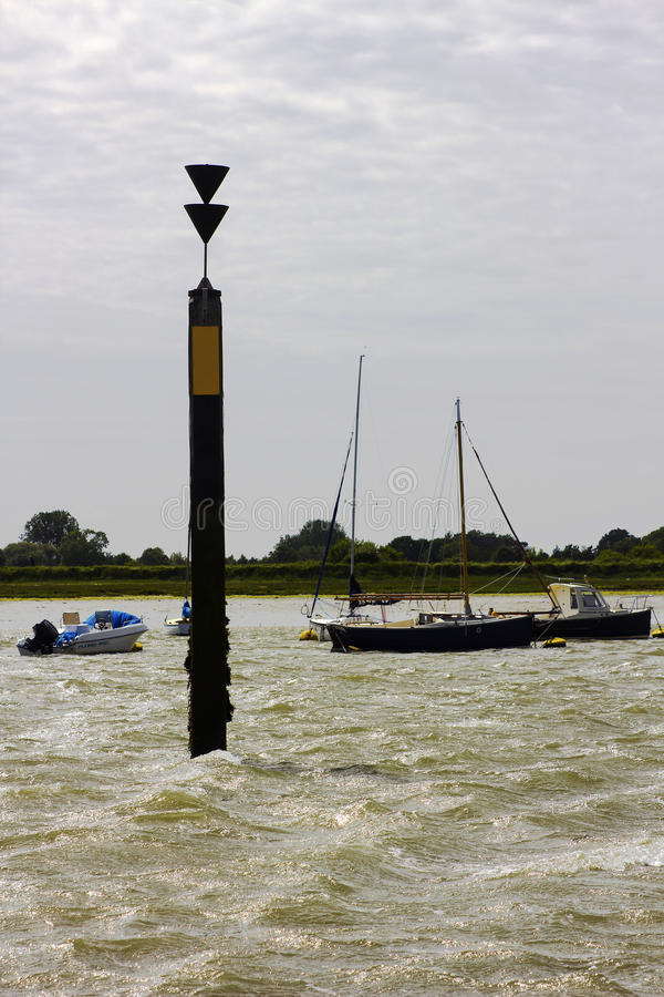 The marker beacon at the entrance to the dredged deep water channel in historic Bosham Harbour in West Sussex in the South of Engl stock photos