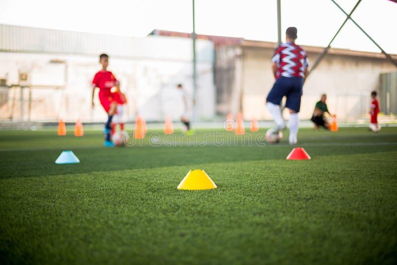 Marker Cone sobre césped artificial verde con jugadores de fútbol infantil borrosos está entrenando antecedentes foto de archivo