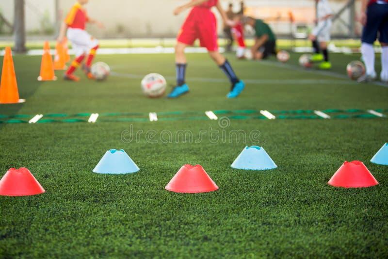 Marker Cone sobre el césped artificial verde con simulacros de escalera borrosa y jugadores de fútbol infantil están entrenando a foto de archivo